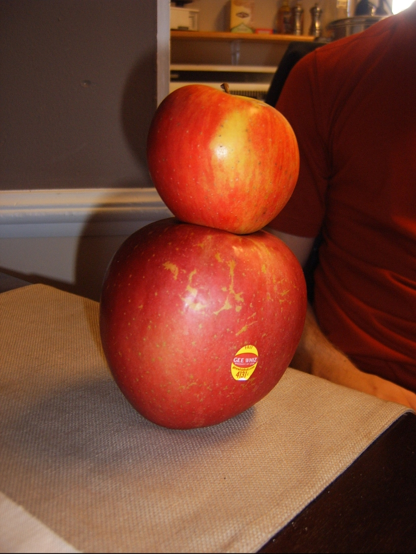 The giant apple with a regular size apple sitting on top of it.